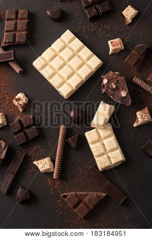 Mix of different kinds of chocolate bars spread all over wooden surface