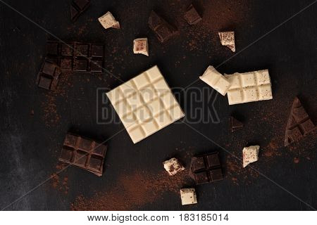 Top view of white and dark crashed chocolate bar blocks spread all over wooden background
