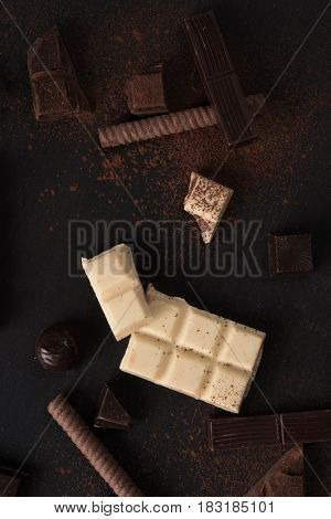 Top view of chocolate bar crashed into pieces and candies over wooden surface