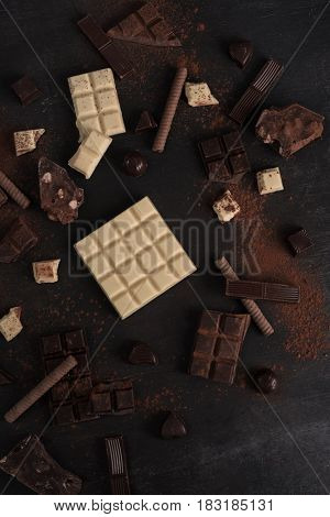Assortment of different types of chocolate bars crashed into pieces over wooden background