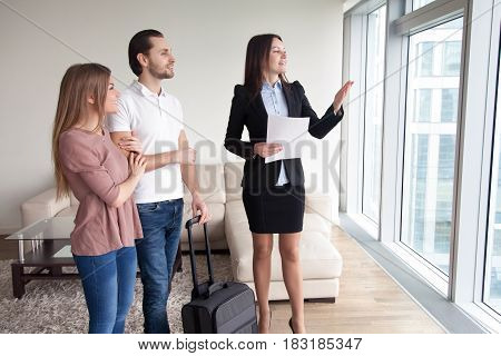 Happy young couple travelers moving in new rented own apartment, standing by the window enjoying view, meeting with female real estate agent showing flat for rent, telling about nearby attractions
