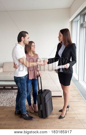 Short-time rent and tenancy. Attractive arriving young couple with travel case bag and broker handshaking after real estate deal, realtor meeting clients, moving in new home, full length vertical