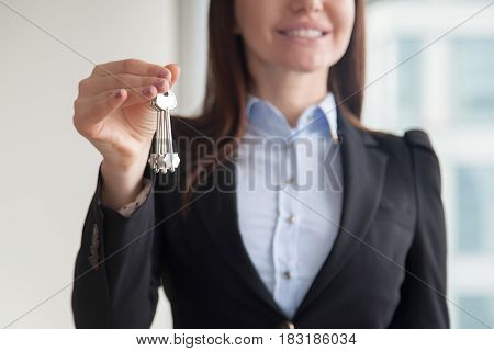 Close up view of attractive smiling friendly female realtor holding keys to apartment or house, buying property purchase concept, first investment house, real estate market, focus on keys
