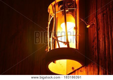electric lamp retro style hanging on bamboo wall in the night