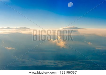 The colorful sky above the clouds with half moon airplane traveling in the summer