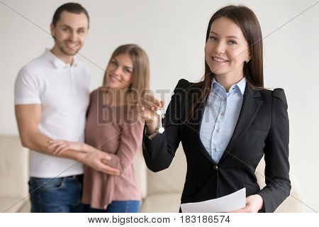Reliable trusted real estate agency. Friendly female broker in the foreground holding keys to new apartment, deal with buyers or renters, applying for mortgage, affordable prices for property poster
