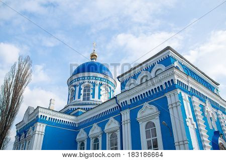 Old blue-white church with blue sky and clouds