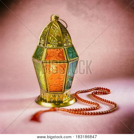 An islamic festive background of lantern and rosary. Grunge, vintage effect.