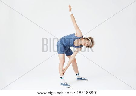 Nice guy bending at waist touching right leg with left hand. Fitness concept. White background