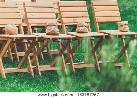 Wedding ceremony. Empty wooden guest chairs standing on pavement in row outdoors on natural summer landscape, nobody, objects