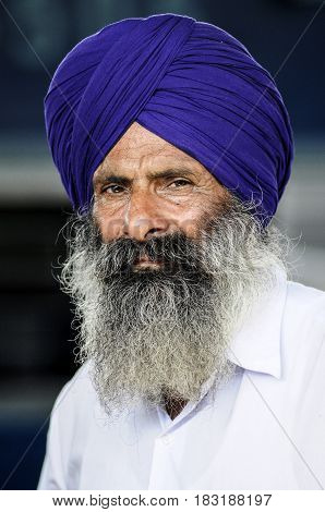 Pathankot India september 9 2010: Face of indian old sikh in violet turban with beard.
