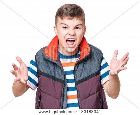 Emotional portrait of irritated shouting teen boy. Furious teenager screaming and looking with anger at camera. Handsome outraged child shouting out loud, isolated on white background.