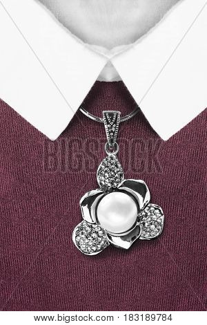 Pearl and diamonds pendant over maroon pullover with white collar closeup