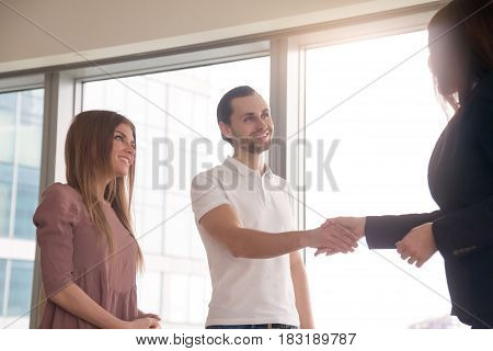 Man and woman came to the office to get consultation. Business people shaking hands, before after successful negotiations, pleasant meeting with agent, notary or lawyer, greeting gesture