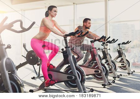 Young happy couple in fitness club. Cardio workout on stationery exercise bikes. Healthy lifestyle, man and woman training in gym. Flare effect