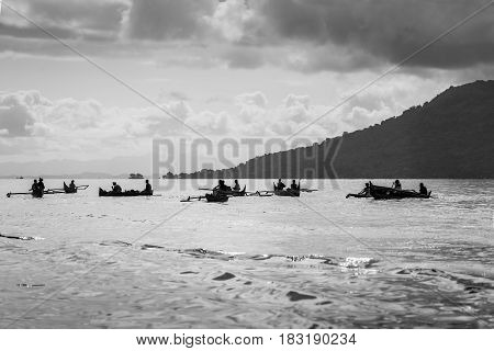 Aboriginal traditional Malagasy pirogue - wooden outrigger canoes (carved from a tree trunk) at sea Nosy Be Island Madagascar black and white photography.