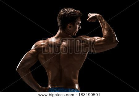 Strong Athletic Man Fitness Model posing back muscles, triceps over black background. Studio shot on black background.