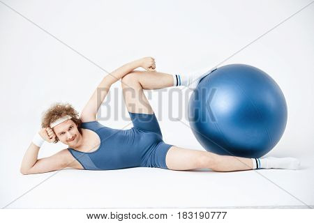 Funny young man posing lying on floor, holding exercise ball with legs. Left hand up