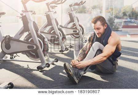Little break. Handsome young man in sportswear relax after training in gym, sit on floor, lacing sneakers shoes. Sexy guy with tattoo in fitness center