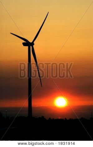 Wind Turbine For Alternative Energy In Sunset - Blurred Blades Due To Rotation