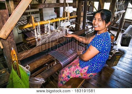 INLE, MYANMAR - MARCH 4 2017: Woman weaving with a loom in water village at  Inle lake on March 4, 2017, Myanmar. (Burma)