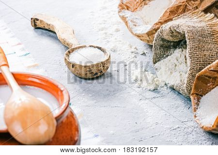 Packs of flour and sugar, rustic wood spoons and clay pot of milk on the concrete background. Close up