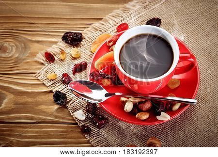 Red ceramic cap with hot coffee on wooden boards and dried fruits.