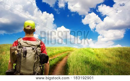 Young man hiking a path leading to the horizon on the open countryside with beautiful clouds in the deep blue sky