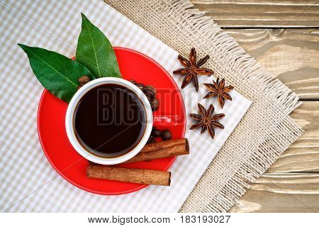 Red ceramic coffee cup with standing coffee on a wooden background. With cinnamon and coffee beans.