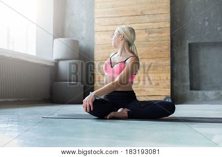 Woman in half-turn Lotus pose, parivrtta Ardha Padmasana. Athletic girl practicing yoga or pilates workout indoors, full length