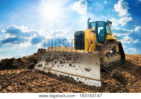 Yellow excavator on new construction site with the bright sun and nice blue sky in the background