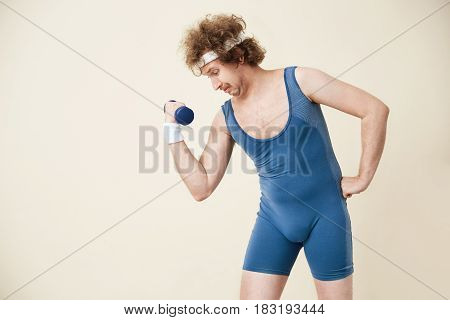 Out of date sport clothing. Man working on arm muscles, training with ligh dumbbell