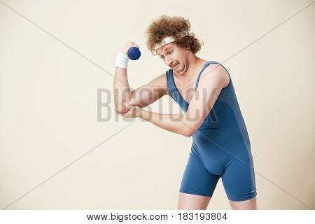 Weak young man in jumpsuit can't make it. Working out hard with ligt dumbbell