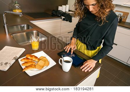 Curly woman ready to go out using electronic tablet while having fast breakfast in the kitchen