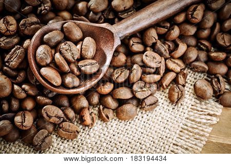 Coffee beans in brown spoon on sackcloth. Closeup.