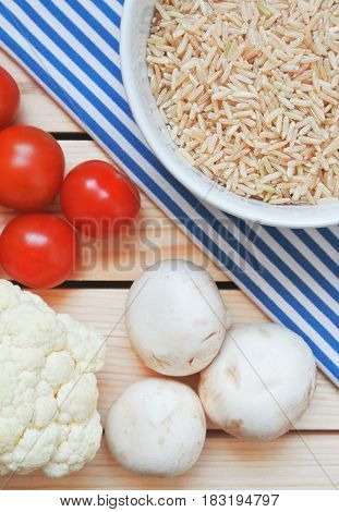 Healthy vegan food for making dinner, meal. Brown rice, cauliflower, cherry tomatoes and mushrooms on wooden table.