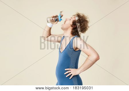 Side shot of thursty man drinking water from glass bottle. Retro sport clothing. Sport concept