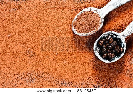 Cocoa powder scattered as background. Rustic wooden spoons full of cacao powder and coffee beans. Top view