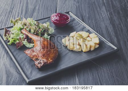 Duck confit. Roasted leg served with apples and cherry sauce. Restaurant food on black wood table