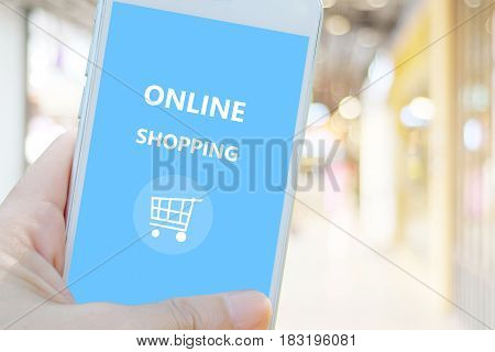 Hand holding smart phone with online shopping device on screen over blur store background business and technology online shopping digital marketing concept