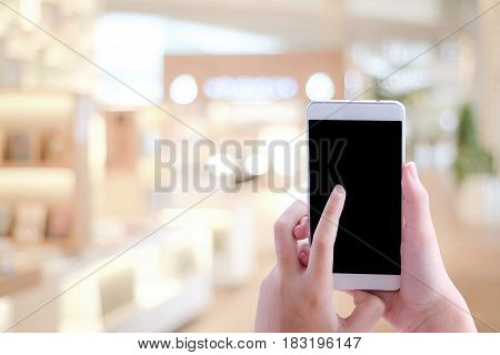 Hand using smart phone over blur store with bokeh light background banner business and technology concept digital marketing seo e-commerce lifestyles