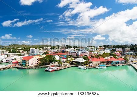 St. John Antigua - March 05 2016: bay with cute houses at harbor with yacht boat ship transport in sea ocean water blue cloudy sky sunny summer on natural background. traveling and vacation