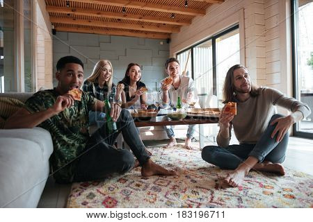 Five friends are sitting in house and eating pizza  while rapturously looking away