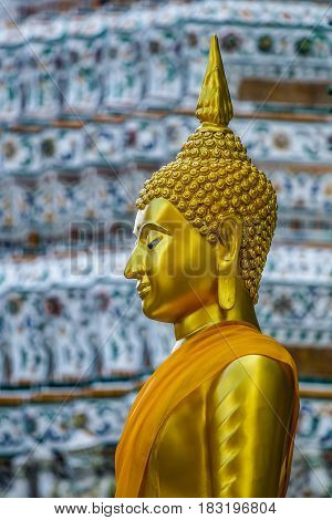 Side view of golden Buddha image with Wat Arun temple pagoda background in Bangkok Thailand