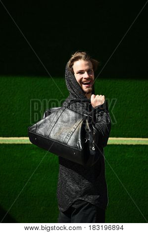 Strong Sportsman With Sport Leather Bag On A Green Background