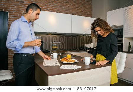 Young couple looking news in newspaper and electronic tablet while having fast breakfast in home before go to work