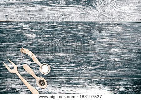 Black and white wood background with handmade wooden fork and spoons full of salt and pepper. Top view