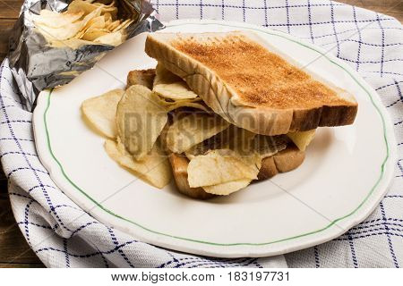 toast bread with butter and potato crisps on a plate