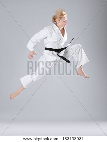 Young sporty woman practicing martial arts on light background