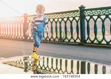 Boy running through puddles in the alley of the Park in the evening.The guy in the denim overalls and yellow sneakers jumping over the puddle.